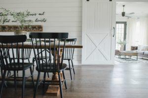 Białe, drewniane drzwi przesuwne oddzielające salon od jadalni